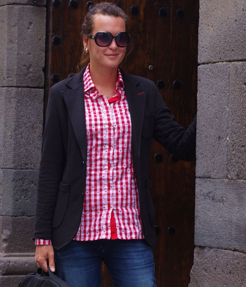woman wearing red gingham shirt with black jacket