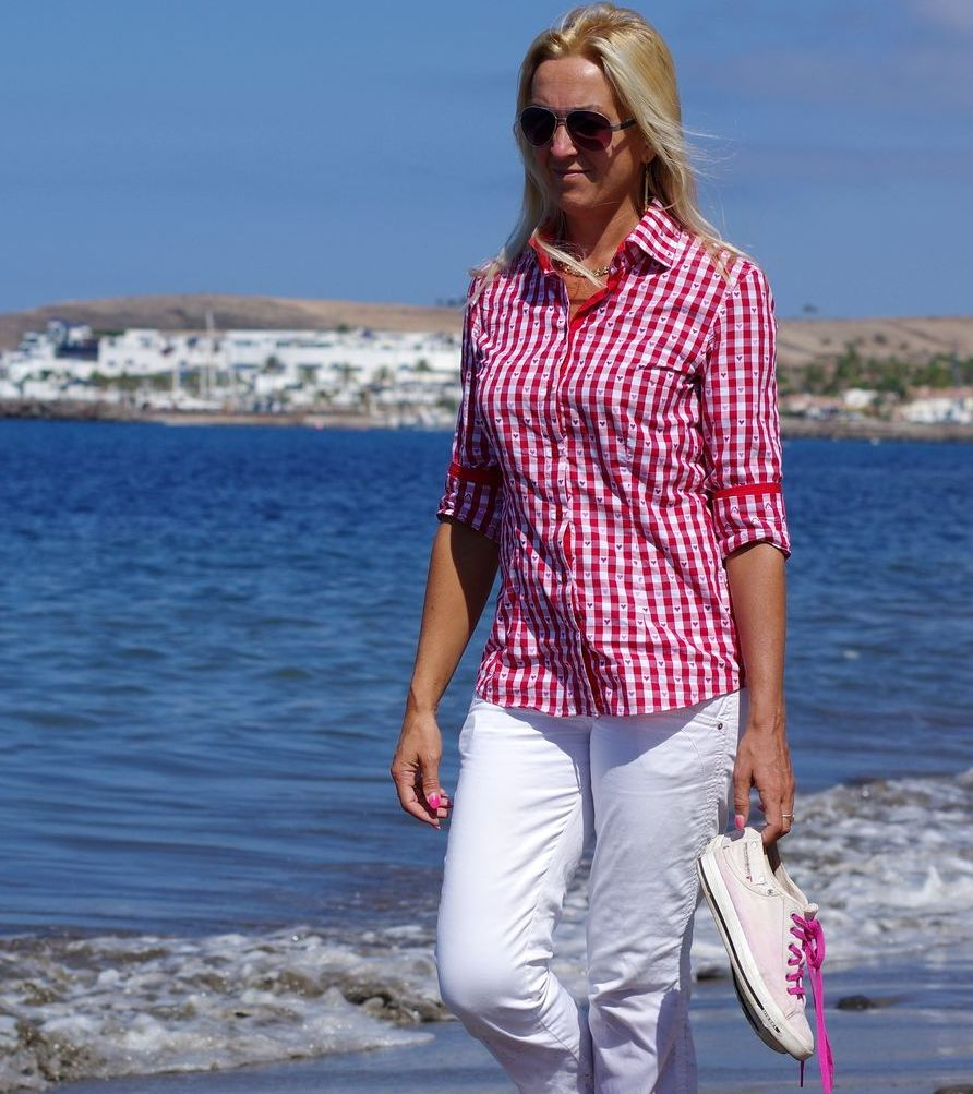 blond woman wearing red shirt with white jeans